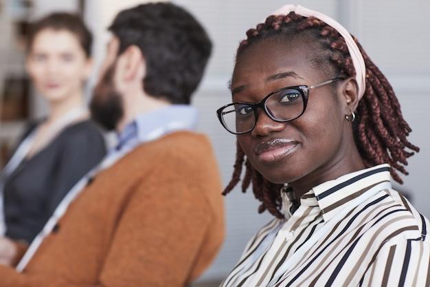 Nahaufnahme des porträts einer jungen afroamerikanischen frau, die eine brille trägt und die kamera anschaut, während sie im publikum auf einer geschäftskonferenz oder einem seminar sitzt, platz kopieren