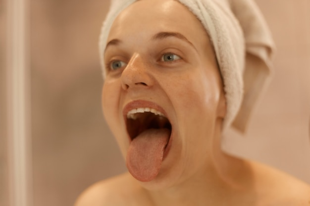 Nahaufnahme des porträts einer jungen erwachsenen schönen frau, die im badezimmer posiert, ihre zunge zeigt, in ein weißes handtuch gewickelt wird und morgens zu hause hygienische verfahren durchführt.