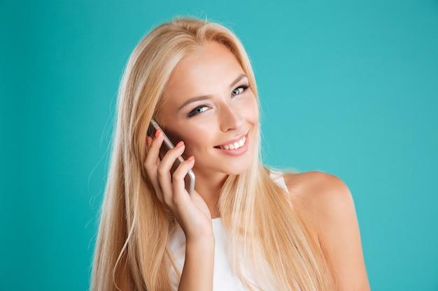 Nahaufnahme des porträts einer lächelnden schönen blondine, die auf dem handy spricht und die kamera einzeln auf blauem hintergrund betrachtet