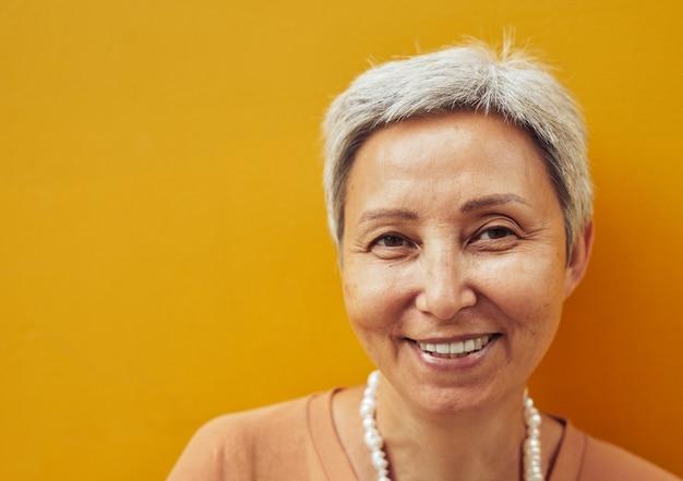 Nahaufnahme des porträts einer selbstbewussten reifen frau, die vor gelbem hintergrund posiert und in die kamera schaut, platz kopieren