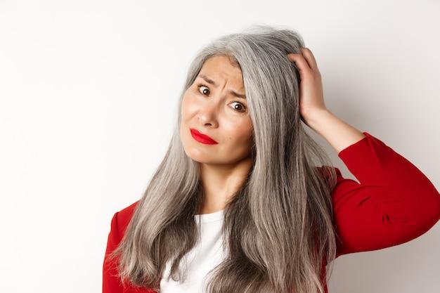 Nahaufnahme des porträts einer verwirrten asiatischen managerin, die sich am kopf kratzt und in die kamera schaut und auf weißem hintergrund steht