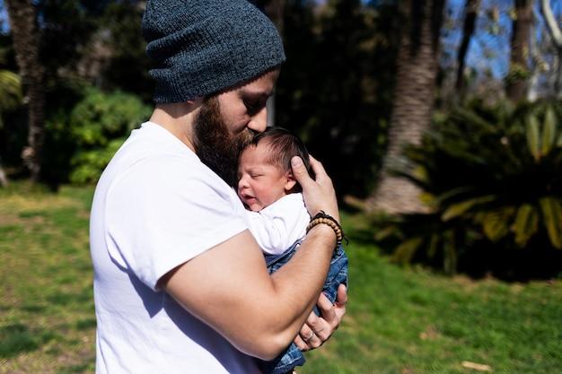 Nahaufnahme des porträts eines glücklichen jungen vaters, der sein süßes, entzückendes neugeborenes kind umarmt und küsst.