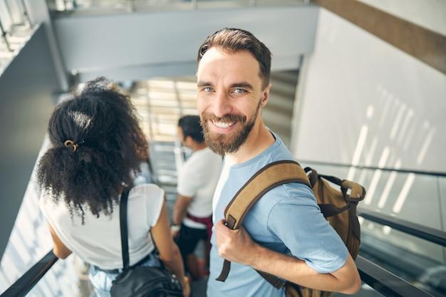 Nahaufnahme des porträts eines gutaussehenden mannes in blauem hemd mit rucksack auf der schulter, der zum abflug am gate für reisen mit dem flugzeug geht