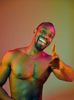 Nahaufnahme des porträts eines jungen nackten afrikanischen mannes, der die kamera im haus betrachtet