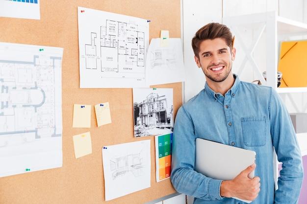 Nahaufnahme des porträts eines lächelnden mannes, der an der aufgabentafel steht und einen laptop hält