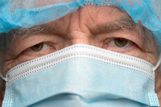 Nahaufnahme des porträts eines traurigen älteren erwachsenen, der in einer chirurgischen gesichtsmaske mit ohrriemen gekleidet ist und die nase von sars bedeckt, virulent ansteckende krankheit corona-virus. traurige augen des mannes während der pandemie, quarantäne.
