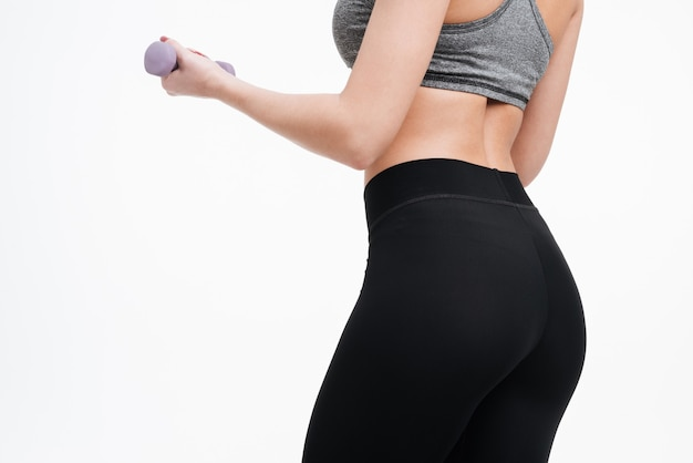 Nahaufnahme des porträts eines weiblichen, fitten körpers, der mit hanteln auf einem weißen hintergrund trainiert