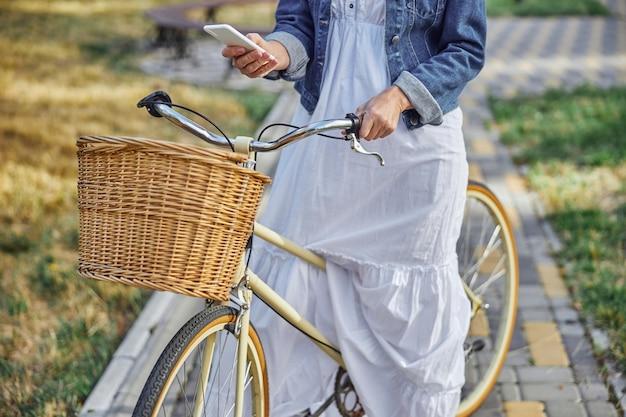Nahaufnahme des porträts von weiblichen händen, die einen lenker eines citybikes mit korb und handy halten, während sie zeit auf dem boulevard verbringen
