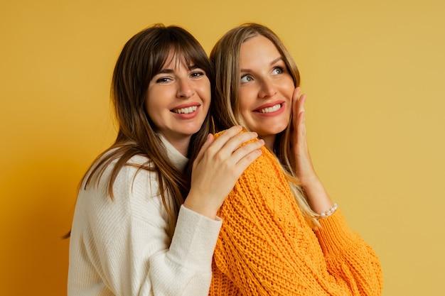 Nahaufnahme des porträts von zwei hübschen frauen in gemütlichen pullovern, die auf gelb posieren. modetrends im herbst und winter.