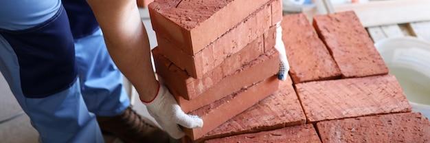Nahaufnahme des professionellen arbeiters, der rote ziegelsteine auf baustelle anhebt. männchen in schutzhandschuhen und gelber helmbauwand. vorarbeiter und box mit arbeitsmitteln