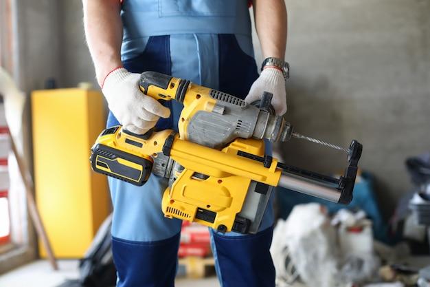 Nahaufnahme des professionellen baumeisters in uniform mit bohrhammer. reparaturfachmann, der reparaturen im haus mit speziellen ausrüstungen durchführt. restrukturierungs- und baukonzept