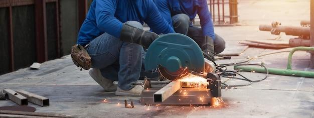 Nahaufnahme des professionellen fokussierten zwei-arbeiter-mannes in uniform, der an der metallrohrskulptur mit einem elektrischen schleifer arbeitet, während funken in der industriellen außenstandortkonstruktion fliegen.