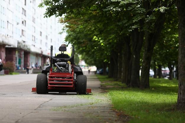 Nahaufnahme des professionellen rasenmähers mit arbeiter nach dem schneiden des grases im stadtpark. gärtner