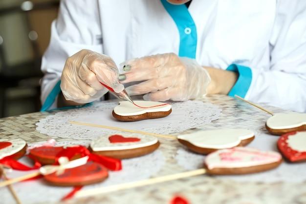 Nahaufnahme des prozesses von handgemalten ingwerplätzchen
