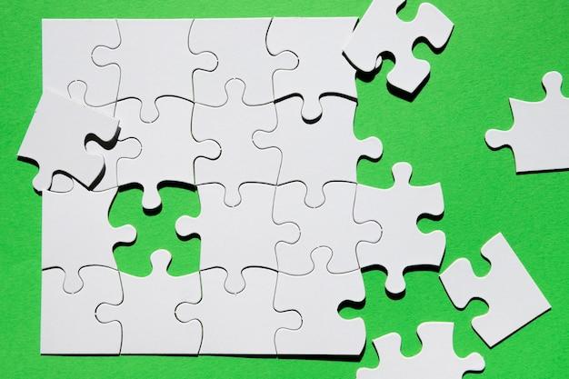 Nahaufnahme des puzzlespielstückes auf grünem hintergrund