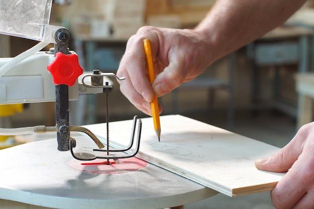 Nahaufnahme des qualifizierten konzentrierten tischlers, der in der werkstatt arbeitet