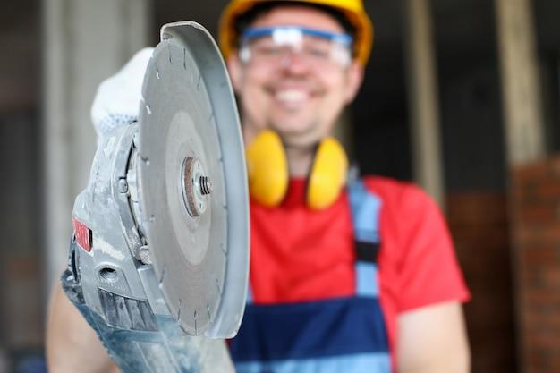 Nahaufnahme des qualifizierten mannes, der professionelle ausrüstung hält. metallscharfer bohrer zur renovierung. lächelnder vorarbeiter in brille und helm. baustellenkonzept