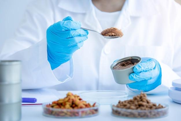 Nahaufnahme des qualitätskontrollpersonals, das die qualität von dosenfutter inspiziert. physische qualitätsprüfung. qualitätskontrollprozess der tiernahrungsindustrie.