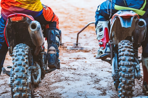 Nahaufnahme des radfahrers sitzend auf motorrad im ausgangspunkt vor dem anfang des rennens