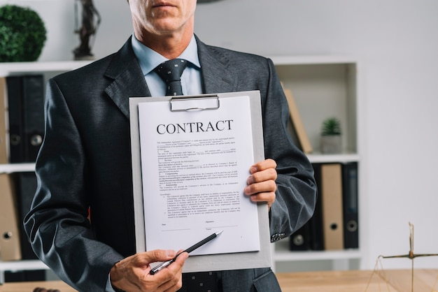 Nahaufnahme des rechtsanwalts legale vertragsvereinbarung mit stift zeigend