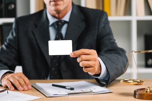 Nahaufnahme des rechtsanwalts weiße leere karte mit vertrag auf tabelle zeigend