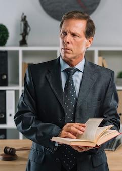 Nahaufnahme des reifen rechtsanwalts gesetzesbuch halten, das weg im gerichtssaal schaut