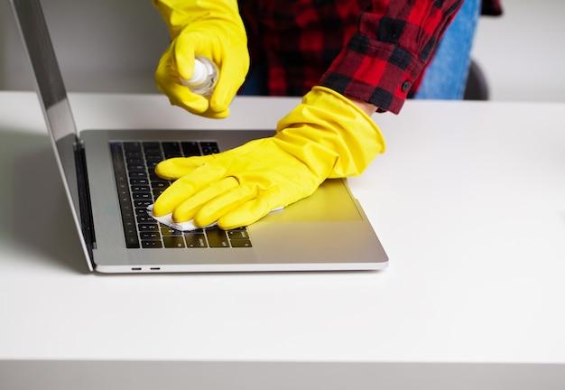 Nahaufnahme des reinigers in gelben handschuhen wischt staub im büro ab