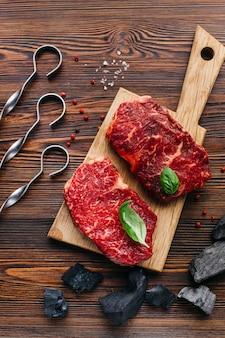 Nahaufnahme des rohen steaks mit kohle und metallischer aufsteckspindel auf hölzernem hintergrund