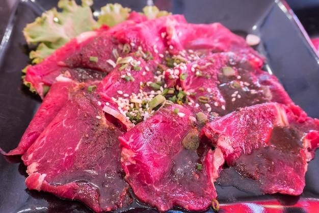 Nahaufnahme des rosa schweinefleischplättchens auf schwarzblech für shabu und grill