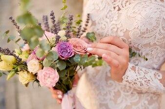 Nahaufnahme des rosa und violetten Hochzeitsblumenstraußes in den Händen der Braut