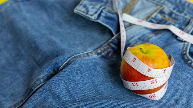 Nahaufnahme des roten apfels auf blue jeans um ein maßband gewickelt