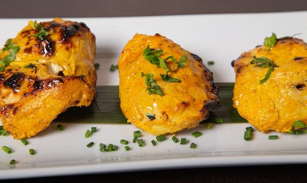 Nahaufnahme des saftigen hühnerspießes, mariniert in joghurt, kardamom, muskatblüte und knoblauch, geröstet in tandoor.
