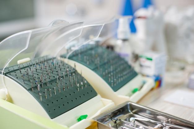 Nahaufnahme des satzes verschiedener zahnmedizinischer bohrer und der zahnmedizinischen ausrüstung