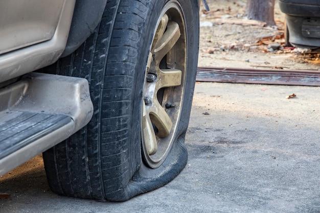 Nahaufnahme des schädigenden platten reifens des autos auf parken.