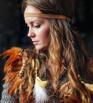 Nahaufnahme des schamanischen weibchens mit indischer feder