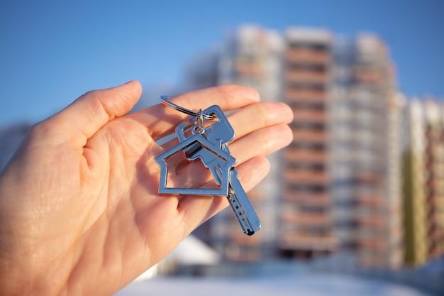 Nahaufnahme des schlüssels mit schlüsselbund in form des hauses in der hand.