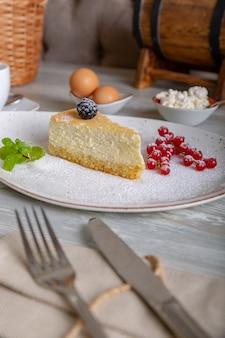 Nahaufnahme des schönen eleganten süßen nachtischs, käsekuchen, serviert auf dem teller. schöne dekoration, restaurantgericht, essfertig. teezeit, gemütliche atmosphäre.