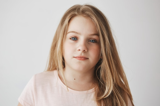 Nahaufnahme des schönen kleinen blonden mädchens mit hellem langem haar und strahlend blauen augen. kind mit entspanntem ausdruck