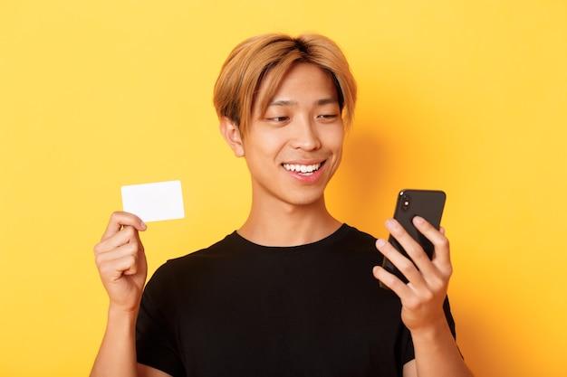 Nahaufnahme des schönen stilvollen asiatischen kerls, der online einkauft, handy betrachtet und lächelt, kreditkarte zeigt, über gelber wand stehend.
