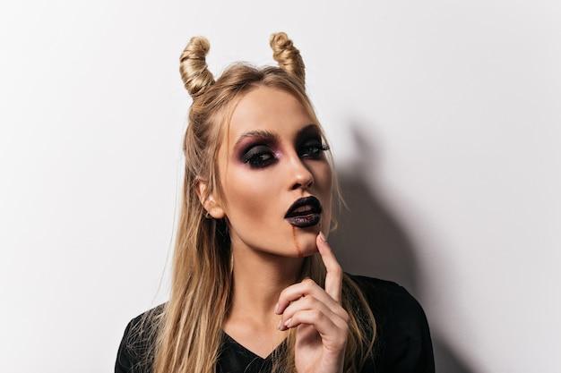 Nahaufnahme des schönen vampirs. innenfoto der dame mit unheimlichem make-up, das in halloween aufwirft.