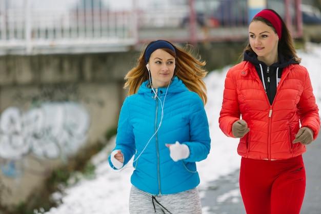 Nahaufnahme des schönen weiblichen athleten zwei, der in winter läuft