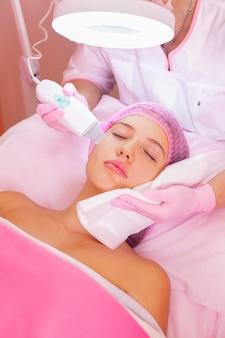 Nahaufnahme des schönen weiblichen gesichts im prozess der ultraschallreinigung und des schälens im kosmetikzentrum