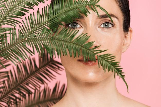Nahaufnahme des schönheitsporträts einer attraktiven, sinnlichen, brünetten, oben ohne stehenden frau, die isoliert steht und mit grünem tropischem blatt posiert