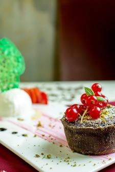 Nahaufnahme des schokoladenmuffins mit roter frischer johannisbeere