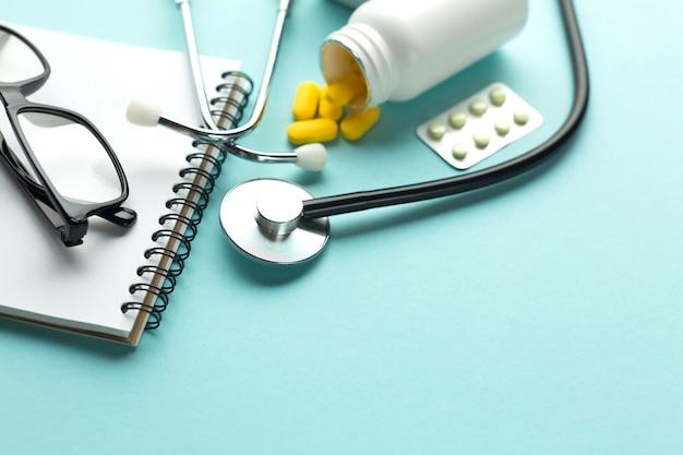 Nahaufnahme des schreibtisches eines doktors mit tabletten und gewundenem notizblock