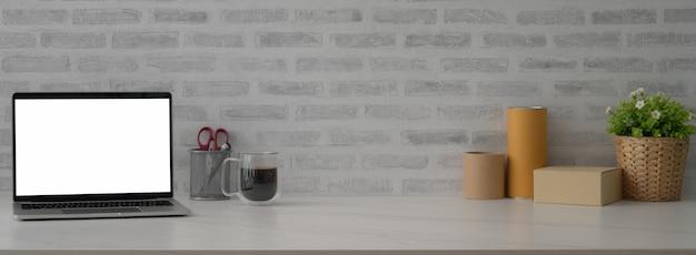 Nahaufnahme des schreibtischs der reederei mit modell-laptop, kaffeetasse, vorräten, kisten und kopierraum