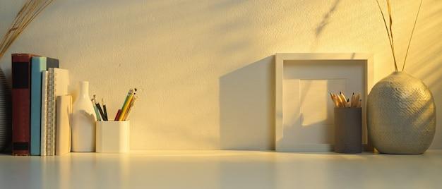 Nahaufnahme des schreibtischs mit büchern, schreibwaren, rahmen, dekorationen und kopierraum im heimbüro