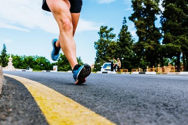Nahaufnahme des schrittes eines erfahrenen läufers gegen den asphaltboden von der ferse