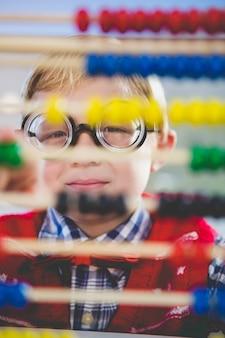 Nahaufnahme des schulkindes, das durch abakus im klassenzimmer schaut