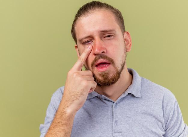 Nahaufnahme des schwachen jungen gutaussehenden kranken mannes, der finger unter auge betrachtet, betrachtet front lokalisiert auf olivgrüner wand